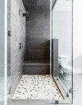 The Botany Bay Sliced Pebble shower floor adds an extra flair to this condo's master bathroom