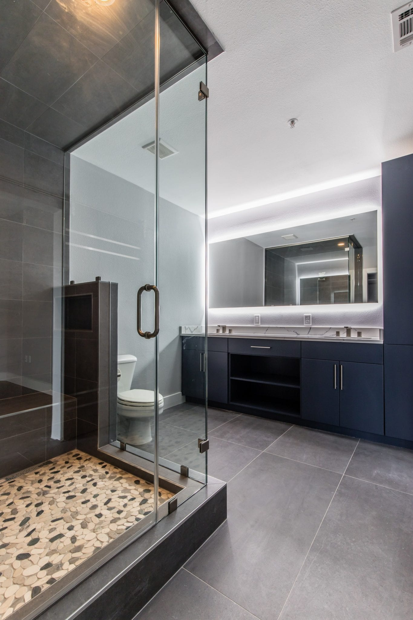 Master Bathroom - Contemporary master bathroom gray tile gray floor and concrete wall, split-pebble shower floor, steam spa bathroom idea with overlay-panel gray cabinets, porcelain white countertop,